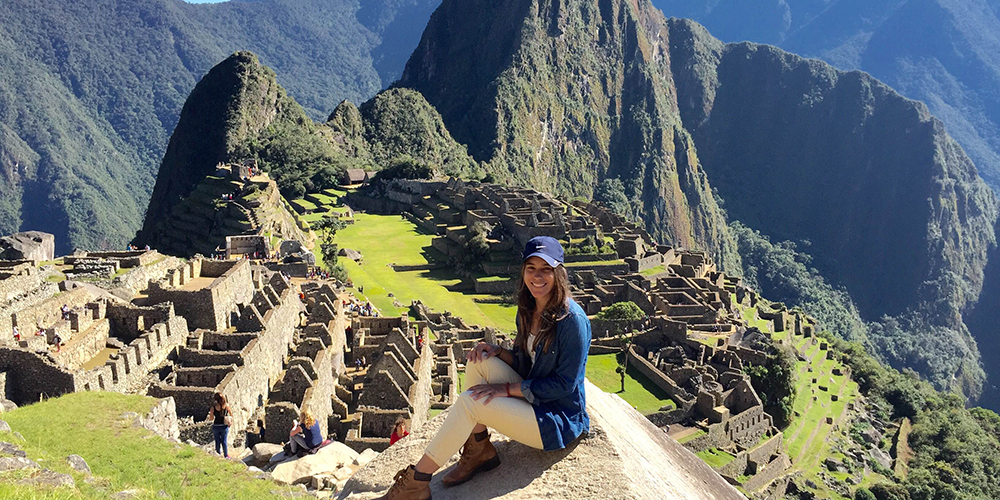 Student sitting on a rock in the foreground, with Machu Picchu in the background.