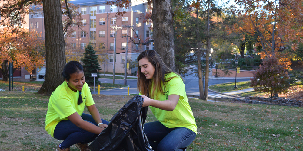 Mount students and Green Team members Jacklyn Hahn and Sirinda Arturi pick up garbage in front of Seton Hall.