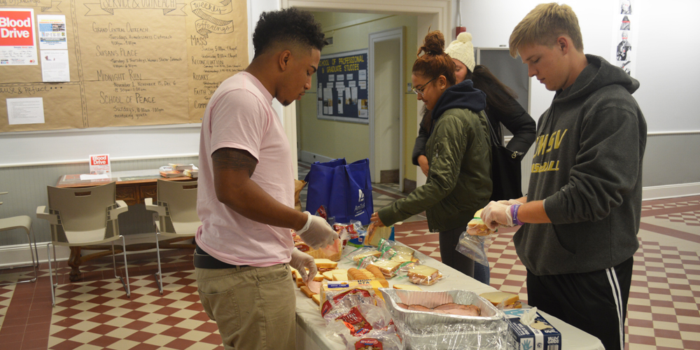Three students make sandwiches for the homeless.