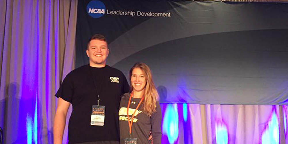 James Fitzgerald '18 and Kelly Gibison 18 pose in front of an NCAA logo.