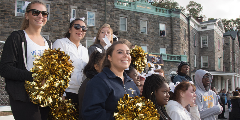 Cheerleaders smiling while watching a soccer game in front of Marillac Hall