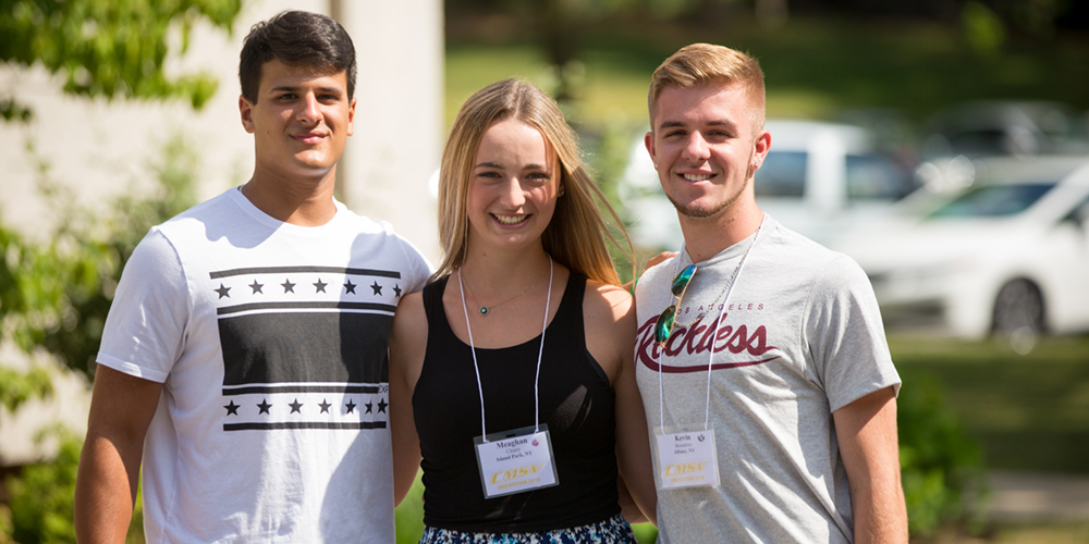 Three students smile at the camera while standing outside on a sunny day.