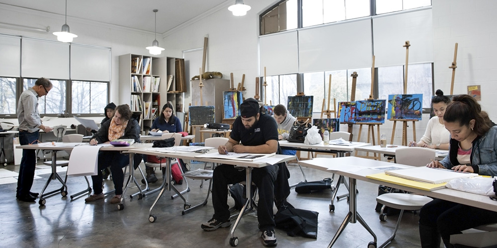 Students drawing in an art studio class.