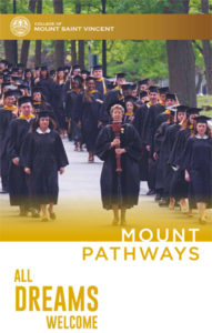 Mount students walk down the hill in their graduation gowns.