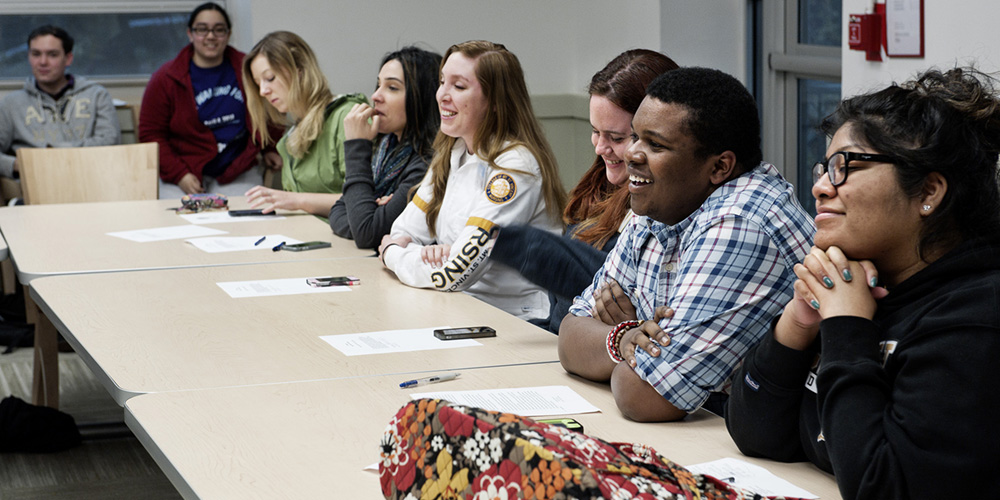 Students smile and discuss in a round-table meeting.