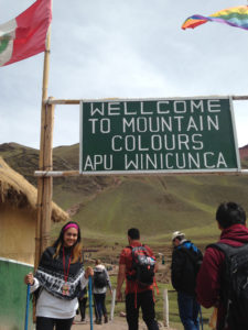 "Leslie Peralta poses with a sign saying ""Welcome to mountain colours APU Winicunca"""