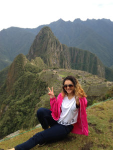 Leslie Peralta sits on a rock with Guatemalan mountains in the background andd shows the peace sign.