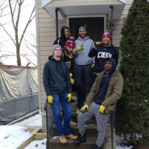Members of the Men's Basketball team pose on the front steps of a house they are rebuilding.