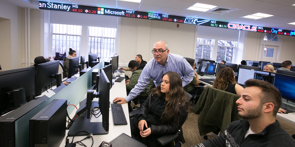 Professor shows two students information on a computer in the Business Trading and Research Center.