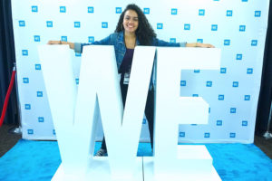 "Katherine Perez '19 poses with the large letters ""WE"""