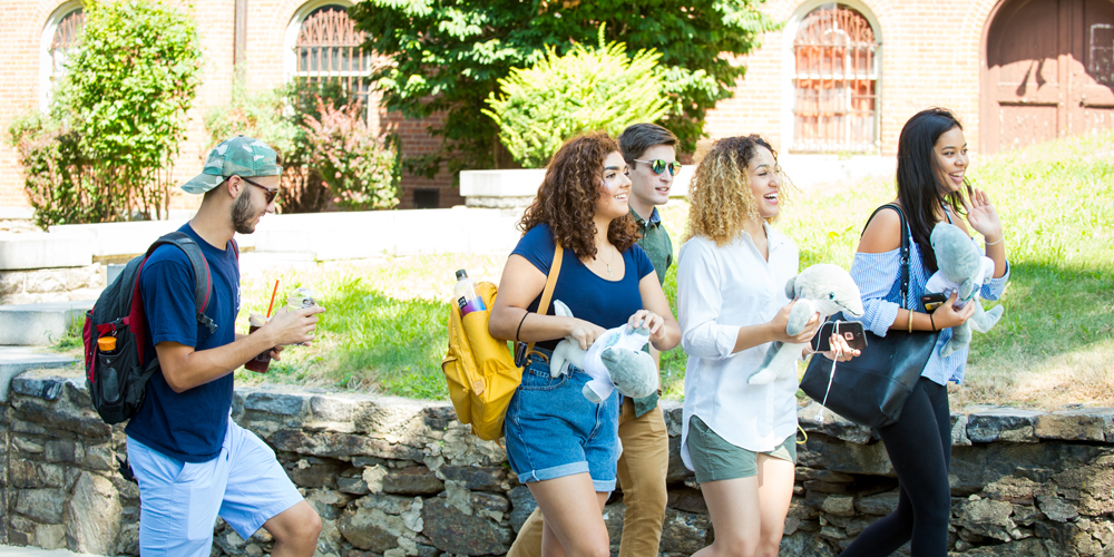 Students walk and smile on campus holding dolphin plush mascots.