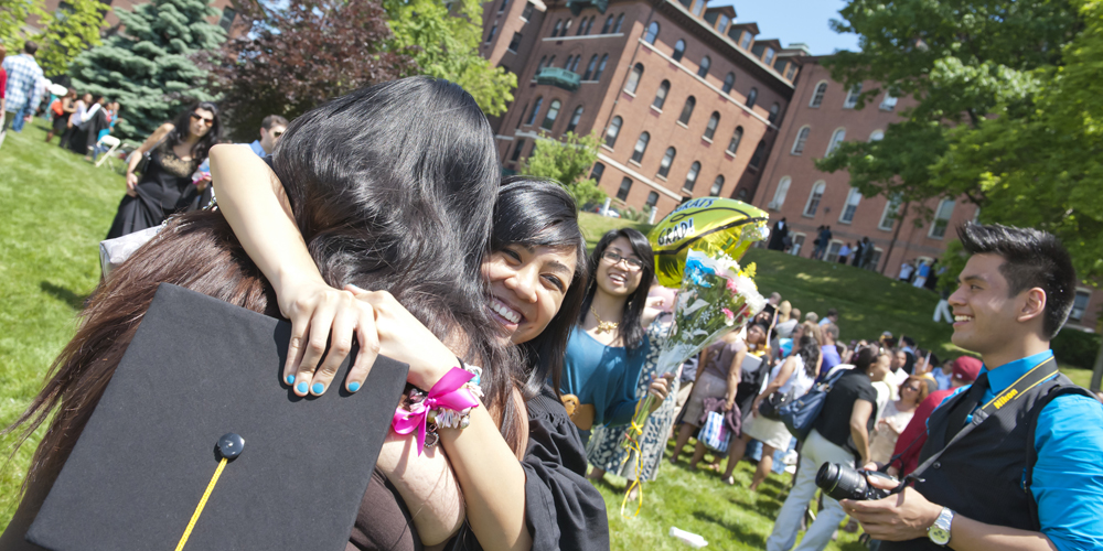 Two girls hug in the forefront on the Great Lawn during Commencement with other students and families smiling in the background.
