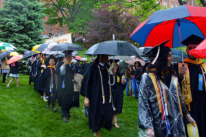 Graduates walk on the Great Lawn holding umbrellas.