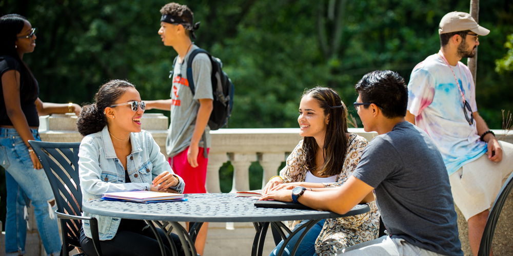 Students smiling and chatting on Seton patio.