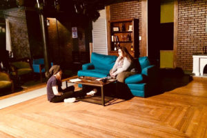 Two student actors talk while one is sitting on a couch and one is sitting on the floor in Stop Kiss at CMSV.