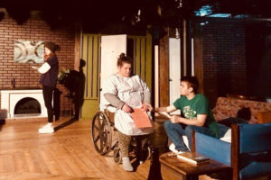 Two student actors talk while sitting while one student stands in the background in Stop Kiss at CMSV.