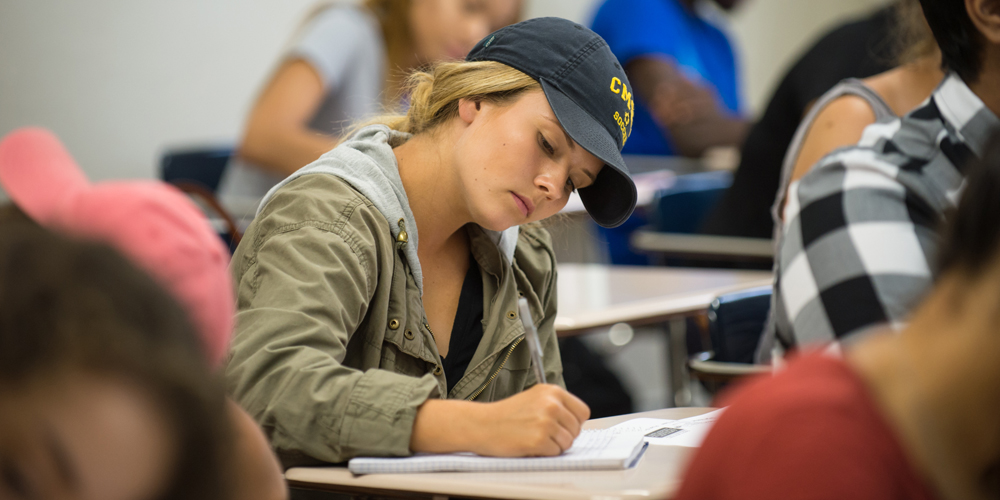 A girl wearing a cap takes notes while in class.