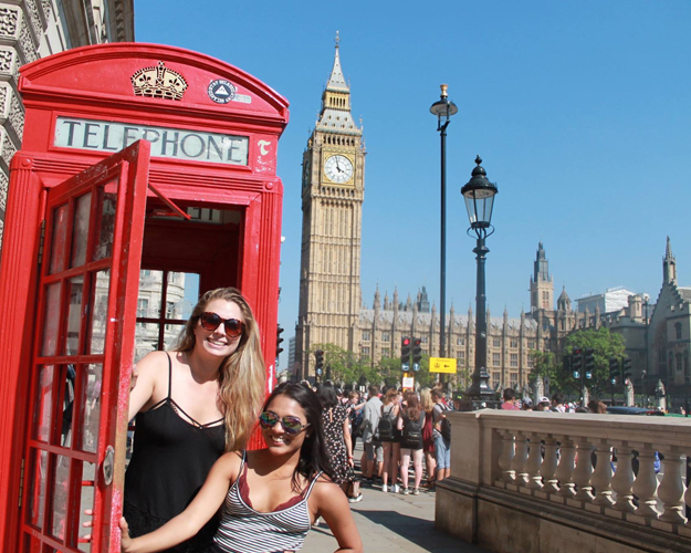 Girls pose next to a London telephone booth.