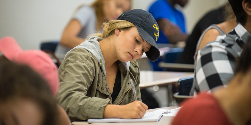 Student takes notes intently in class.