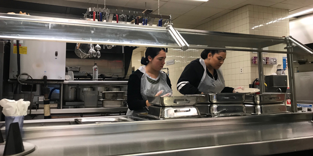 Students volunteer in a soup kitchen.