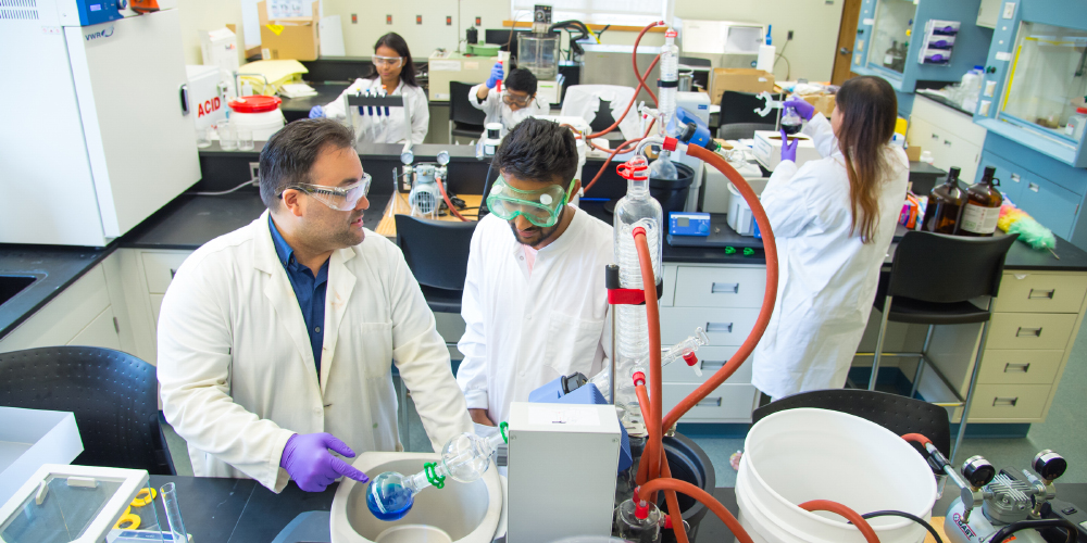Dr. James Fabrizio with students in white coats conducting research in a science laboratory.