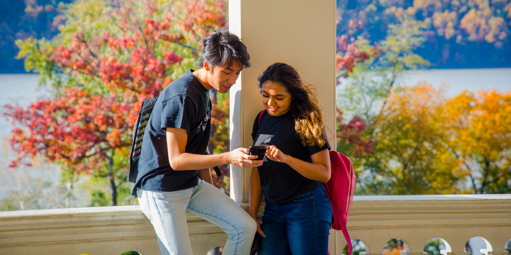 Two students look at a phone on the Founders Hall porch with fall foliage in the background.