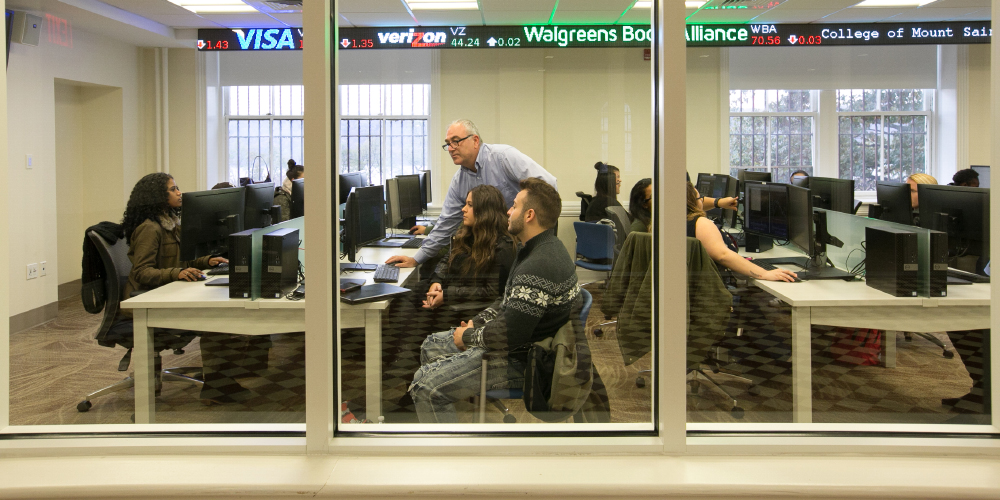 Students with a professor in the business trading room.