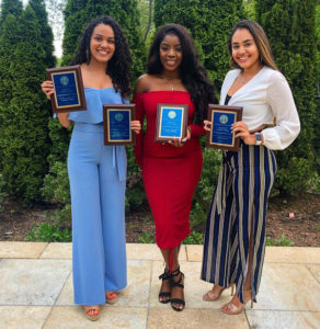 Three students pose with their awards at the Student Affairs Awards ceremony.