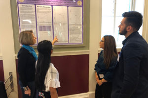 Students and a professor discuss a presentation.
