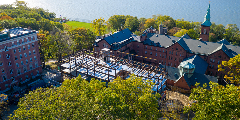 Aerial view of Aquino Hall under construction, Founders Hall, and the Hudson River.