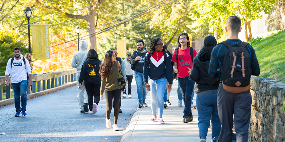Students walking on a sunny day on campus.