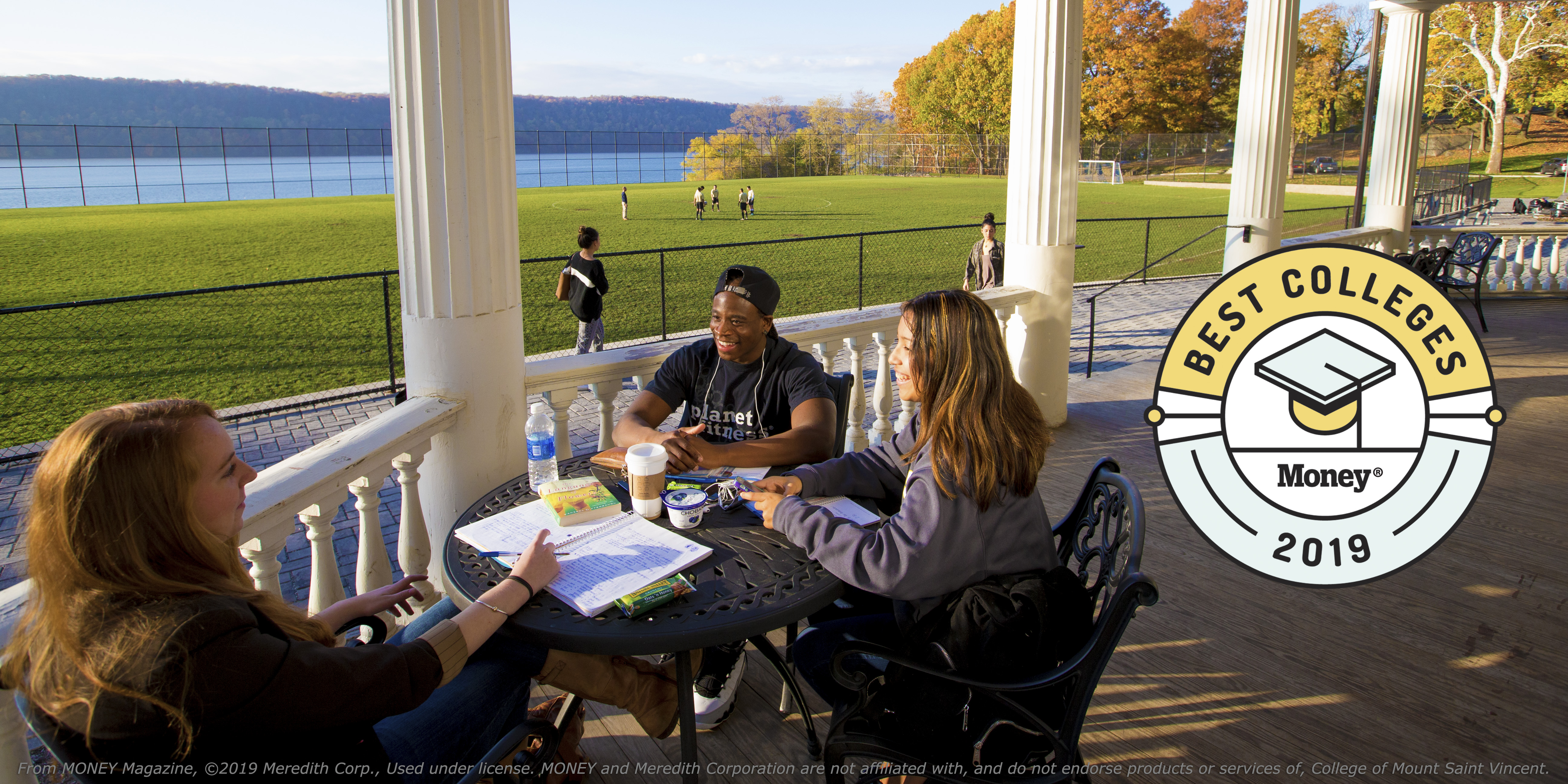 Students smiling and talking on the porch overlooking the field and the Hudson River.