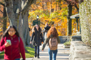 Students walk on campus on a fall day.