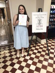 Christina Rasmussen '20 with a Lambda Pi Eta diploma.