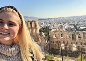 Caitlin Kessel '20 poses with Ancient Greek buildings.