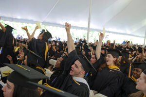 Graduates cheer in the Commencement tent.