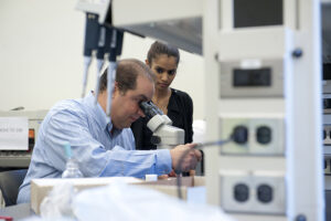 Dr. Fabrizio looks at a microscope and a student watches.