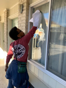 Student cleaning a window.