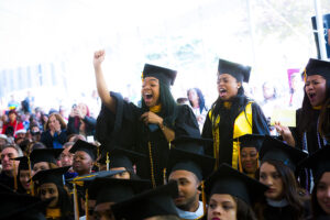 Girls wearing Commencement outfits cheer in the graduation tent.