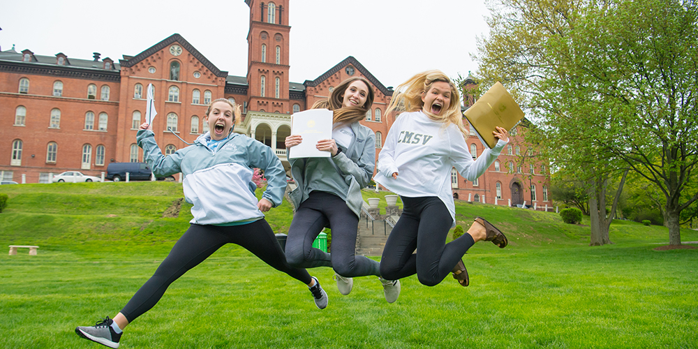 Three girls jump on the Great Lawn.