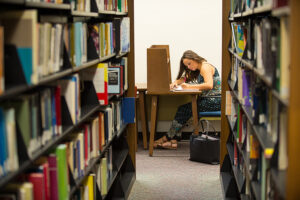 Student writes in the Elizabeth Seton Library.