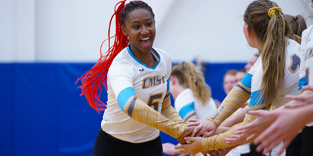 Mount athlete smiling on the court while high-fiving her team mates.