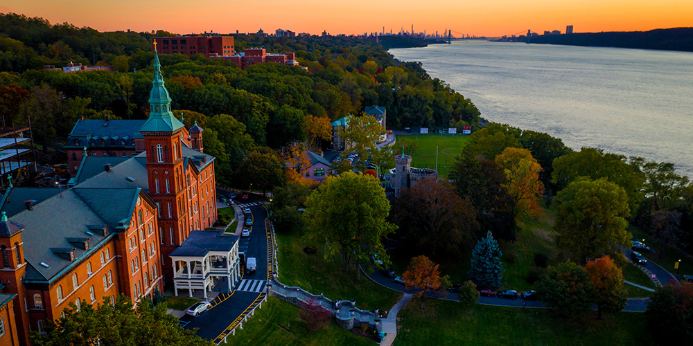 Aerial view of campus and the Manhattan skyline at sunset.