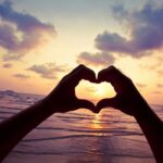 Person makes a heart with their hands with the sky as the background.