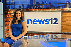 Michelle Ross and the News 12 sign.